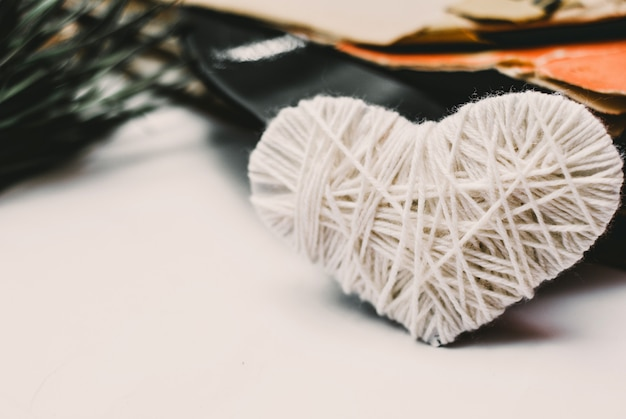 White knitted heart and stack of scratched dusty old vinyl records tied with rope Premium Photo