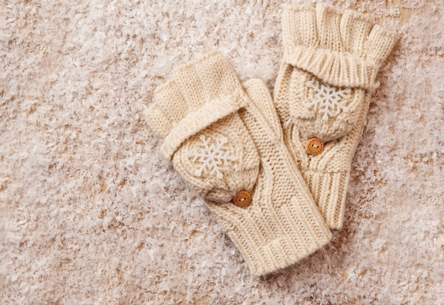 White knitted mittens in the snow Premium Photo
