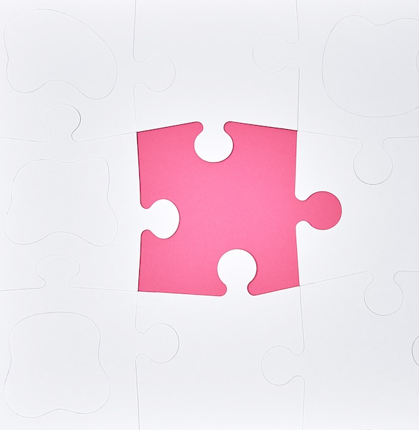 White large blank puzzles on a pink background, top view Premium Photo