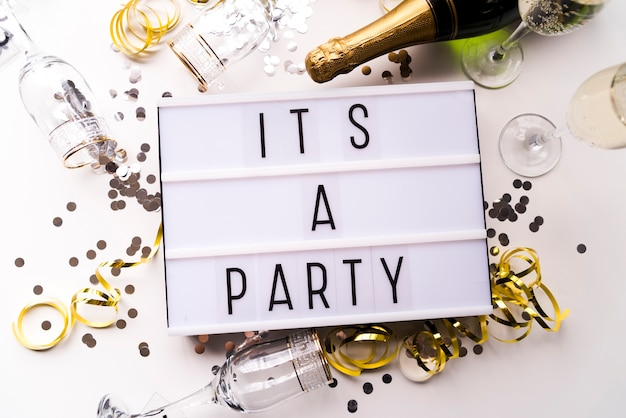 White light box with it's a party text and champagne bottle over white backdrop Free Photo