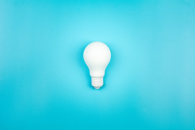 White light bulb is shine on blue table. business growth Premium Photo