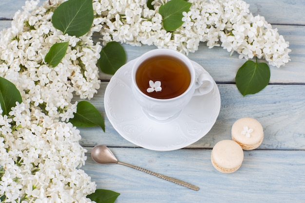 White lilac, cup of tea and macaroons Premium Photo