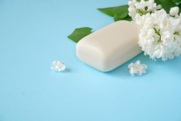白いライラックの花と青い背景の石鹸自然化粧品の概念 Premium写真