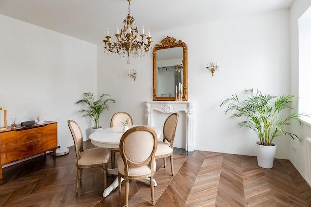 고전적인 장식, 거울, 벽난로, 식탁이있는 흰색 거실. 프리미엄 사진