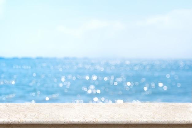 흐리게 Bokeh 바다와 푸른 하늘 흰 대리석 테이블 탑 프리미엄 사진