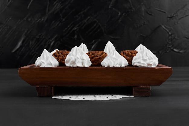 木製の大皿にココアプラリネを添えた白いマシュマロ。 無料写真