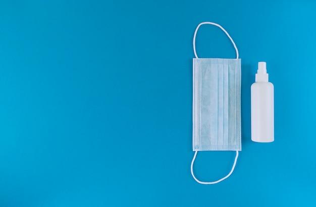 Белая медицинская маска и дезинфицирующее средство для рук во флаконе с распылительным колпачком справа от синей поверхности. простая плоская планировка с копией пространства. медицинская концепция. Premium Фотографии