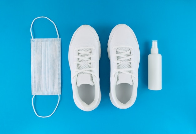White medical mask, trainers, and hand sanitizer on a blue background. monochrome flat lay. quarantine outfit. Premium Photo