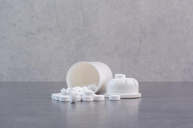 Pillole mediche bianche dal contenitore di plastica. Foto Gratuite