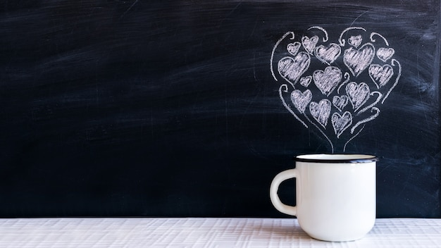 White metal cup and chalk-drawn small hearts in the form of a heart Premium Photo