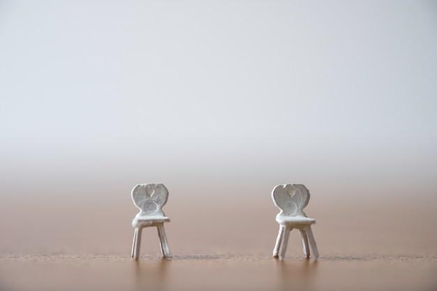 Белый миниатюрный стул позволяет держать людей на расстоянии и предотвращает распространение пандемической инфекции, вызванной коронным вирусом covid-19. концепция социального дистанцирования. Premium Фотографии