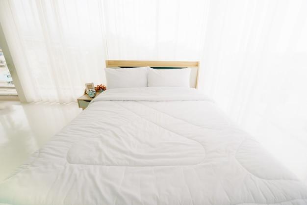 日光と朝の白いシンプルな寝室のインテリア。 Premium写真