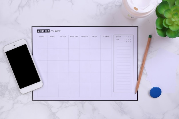 White mockup smartphone and planner schedule on marble background Premium Photo