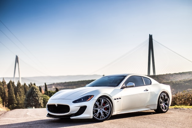 A white modern sport car parking on the road. Free Photo