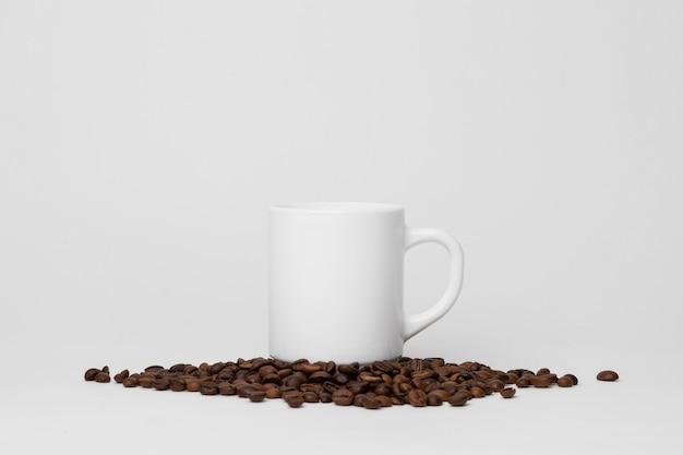 Tazza bianca sulla disposizione dei chicchi di caffè Foto Gratuite