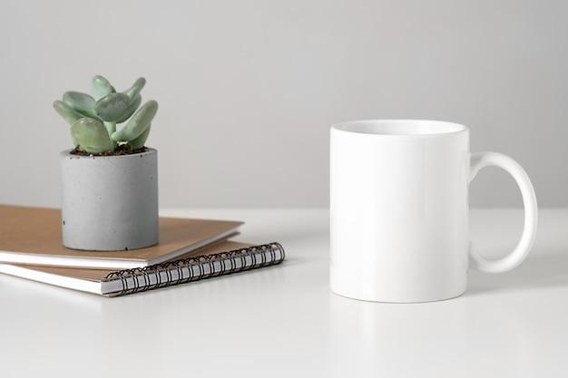 미니멀 한 인테리어, 비즈니스 개념, 즙이 많은 및 메모장의 테이블에 흰색 찻잔 모형. 프리미엄 사진