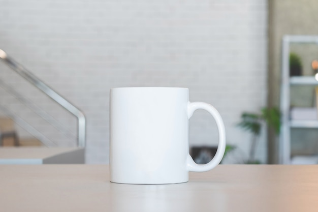 White mug on table and modern room background Premium Photo