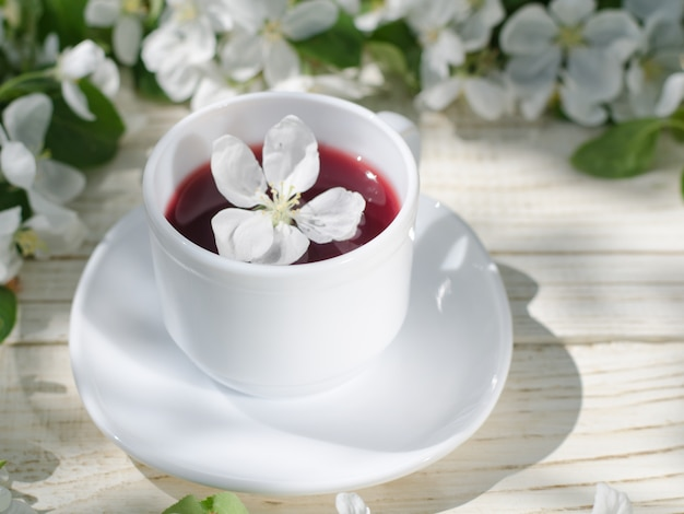 White mug of tea on a wooden table, apple blossoms in the background Premium Photo