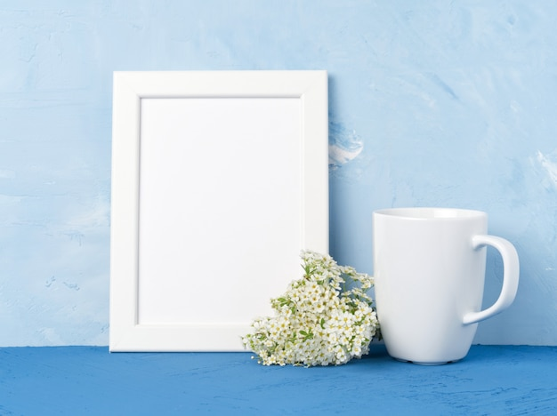 White mug with tea or coffee, frame, flower bouquet on blue table opposite blue wall. Premium Photo
