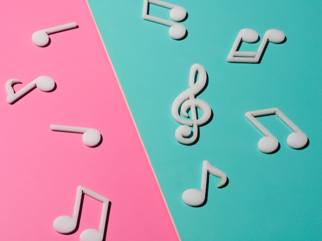 White musical notes on bright colorful background Free Photo