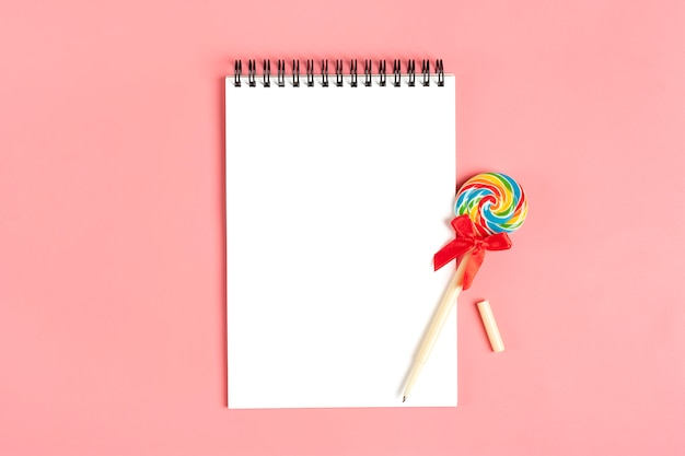 White notebook for notes, pen - lollipop on pink background flat lay Premium Photo