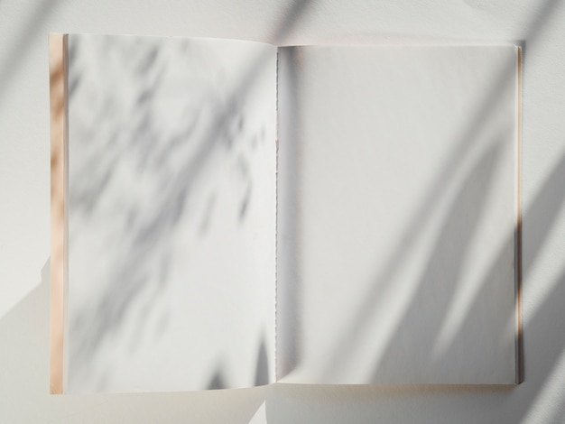 White notebook on a white background with leaf shadows Free Photo