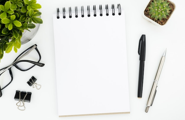 White office desk table with blank notebook page and supplies. top view, flat lay. Premium Photo