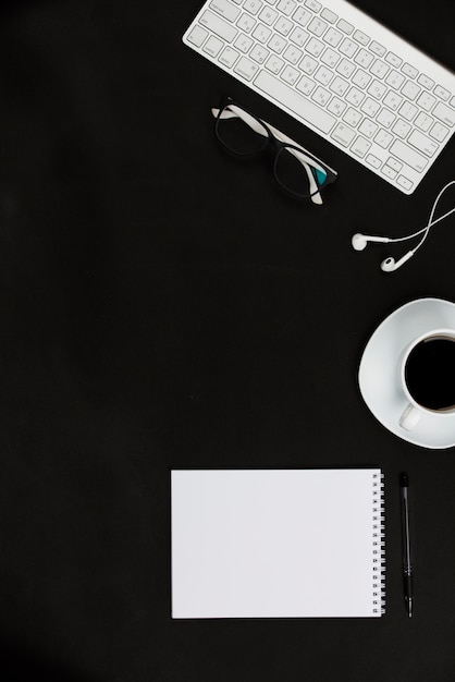 White office supplies and coffee cup on black desktop Free Photo