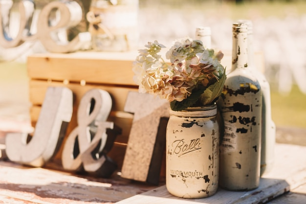 White old bottles with beige flowers stand before wooden Free Photo