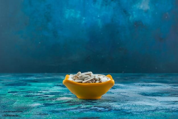 青のボウルに白い有機ヒマワリの種。 無料写真