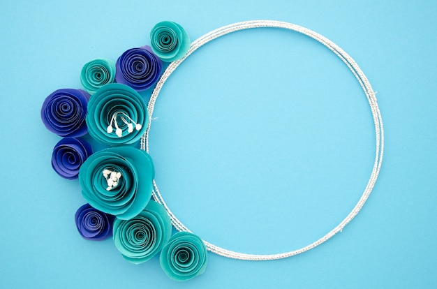 White ornamental frame with blue paper flowers Free Photo