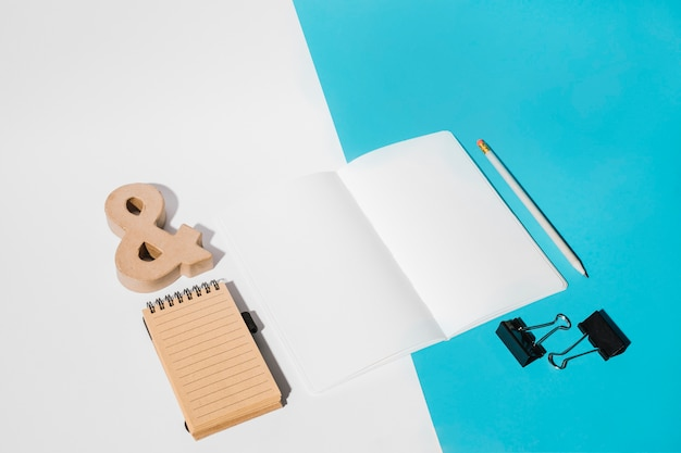White page; bulldog clips; pencil; ampersand symbol and spiral notepad on dual backdrop Free Photo