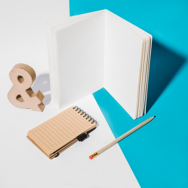 White page notebook; spiral notepad; ampersand symbol and pencil on dual background Free Photo