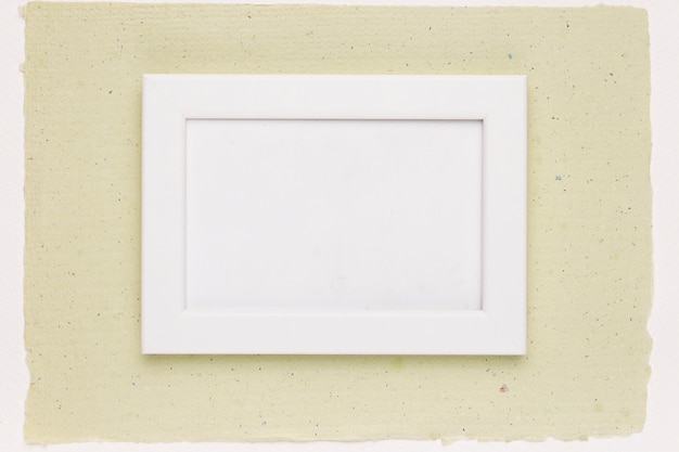 White painted frame on mint green paper Free Photo
