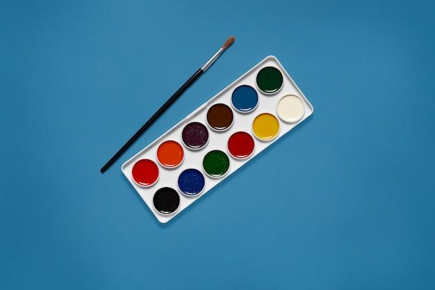 Tavolozza bianca con dodici diversi colori al centro dell'immagine, senza truffa, pennello nero che giace accanto alle vernici. colore blu fantasma. concetto d'arte. attrezzatura necessaria per la verniciatura. Foto Gratuite