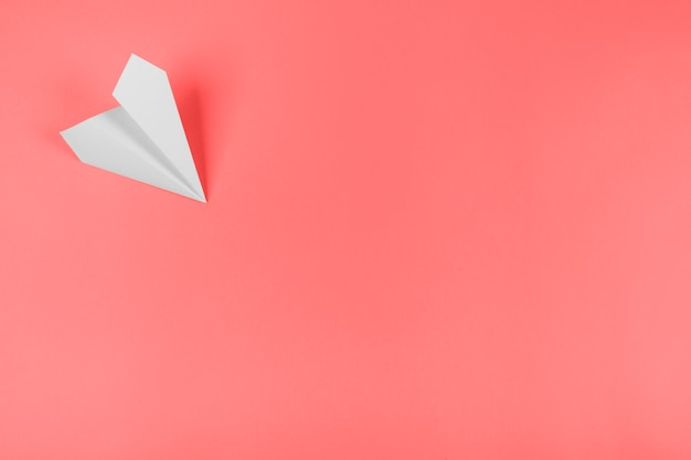 White paper airplane on the corner of the coral background Free Photo
