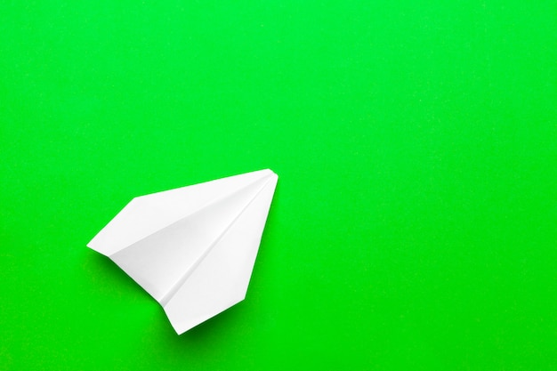 White paper airplane on a green paper Premium Photo