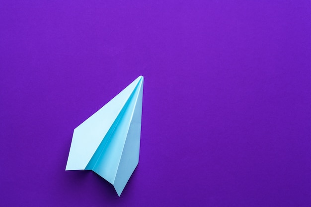 White paper airplane on a purple Premium Photo