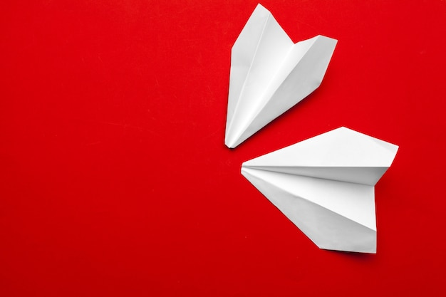 White paper airplane on a red Premium Photo