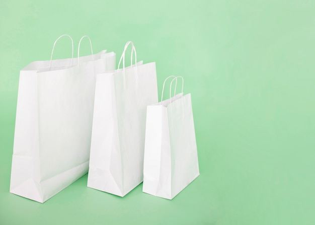 White paper bags on light blue background Free Photo