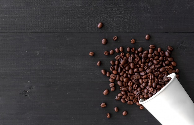 white paper cup and coffee beans on old wooden background