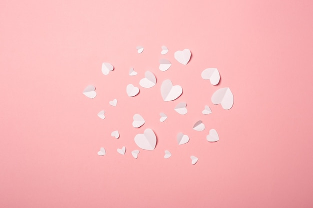 White paper hearts on a pink background. composition of valentine's day. banner. flat lay, top view. Premium Photo