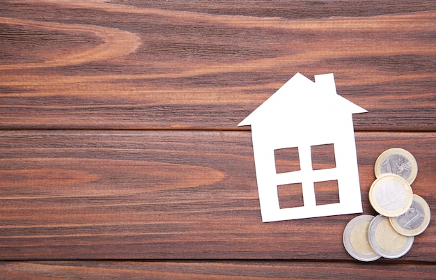 White paper house with coins on brown background Premium Photo