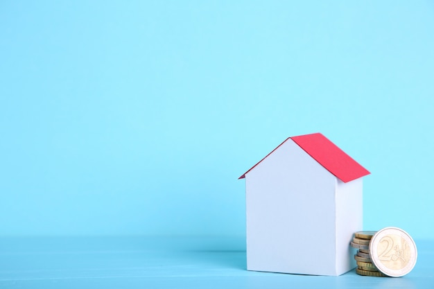 White paper house with red roof, with coins on blue background Premium Photo