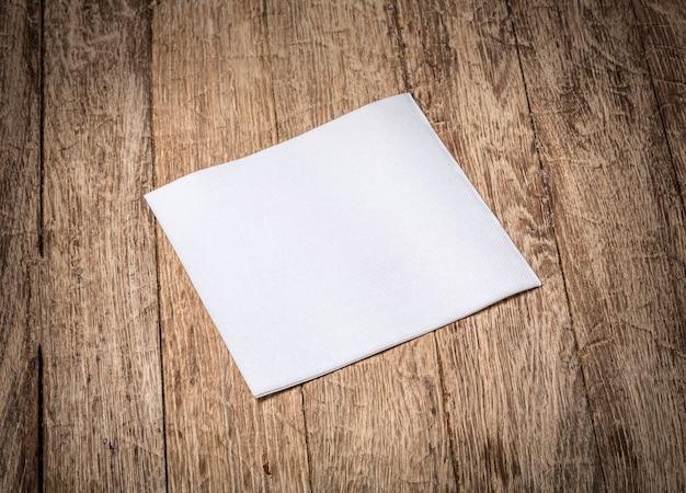 古い木製のテーブルに白い紙ナプキン Premium写真