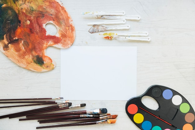 White paper near palettes, knives and paint brushes Free Photo