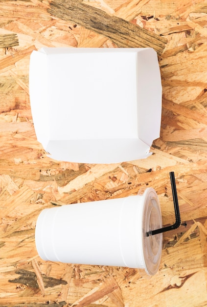 White paper package and disposable drink on textured backdrop Free Photo