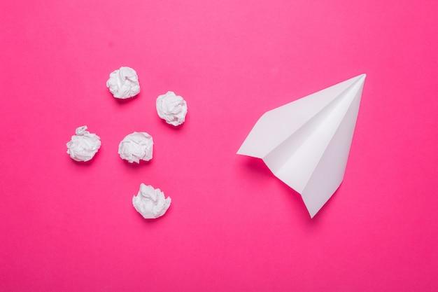백서 비행기와 분홍색 배경에 구겨진 된 종이 공 프리미엄 사진