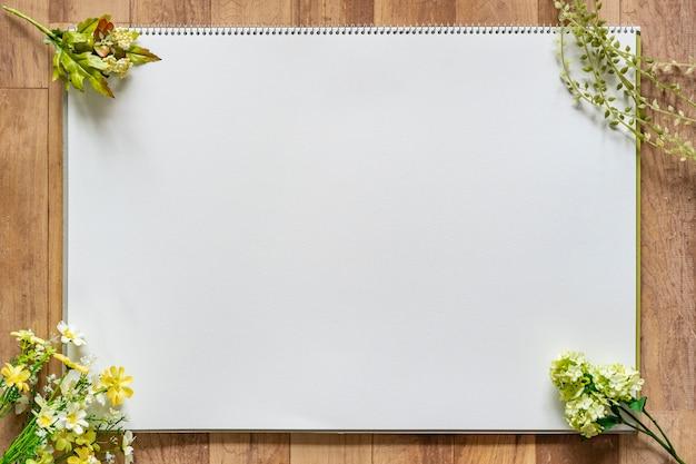 Лист белой бумаги в окружении зеленых Premium Фотографии
