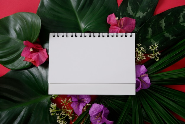 White paper with space for text or picture on red background and tropical leaves and flowers Premium Photo